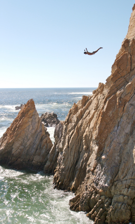 A man cliff dives from a large cliff by the ocean.