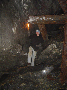 Caving - A man holding a torch while standing next to large iron beams in an abandonded mine shaft.