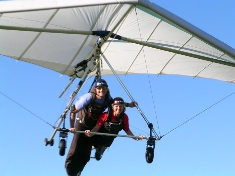 Two people are flying a white hang glider with the blue sky in the background at Wallaby Ranch