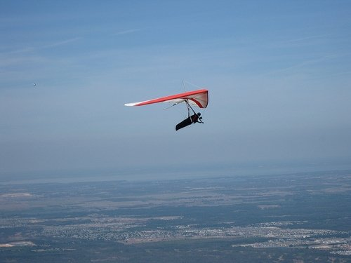 A white hang glider with red outline ascends in the clear evening at Wallaby Ranch.