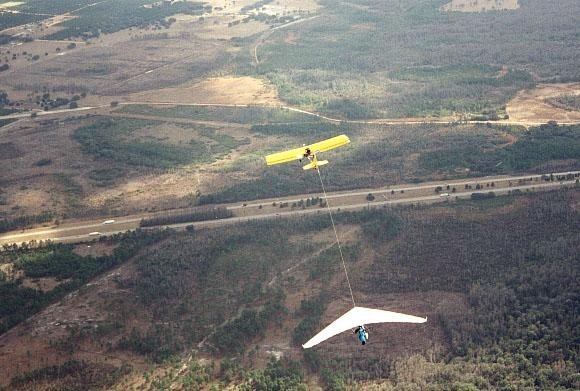 A yellow plane tows a white hang glider at Wallaby Ranch. In the background is a road surrounded by open green land.