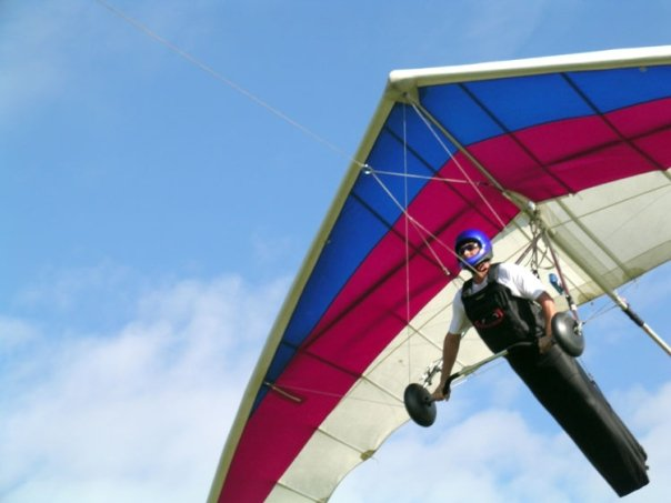 Wallaby Ranch - A man is flying a blue, red and white hang glider with the blue cloudy sky in the background.
