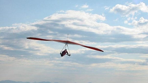 A red hang glider flies in the blue cloudy sky at Wallaby Ranch.